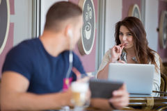 Young man and woman looking at each other in a cafe. Smiling beautiful young women in casual clothes sitting in street cafe with a drink, working on laptop and Stock Photo