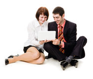 Young man and woman looking at laptop. Young man and woman sitting on the floor, looking at laptop, isolated on a white background Royalty Free Stock Photos