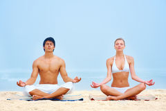 Young man and woman in a lotus position Stock Photography