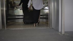 Young man and woman with luggage entering elevator at airport or railway station. Stock footage stock video