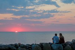 Young man and woman meeting the sunset on the Baltic sea coast royalty free stock photo