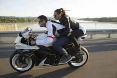 Young man and a woman on a motorcycle. Young men and a women on a motorcycle by day Stock Photo