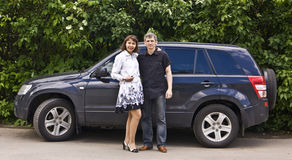 Young man and woman near car. Young man and woman standing near black car (model Sudzuka grand vitara Royalty Free Stock Photo