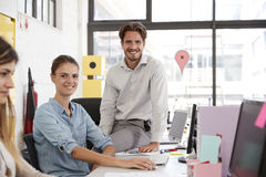 Young man and woman in open plan office looking to camera Stock Photography