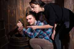 Young man and woman opened a barrel and trying to solve a conund. Young men and women opened a barrel and trying to solve a conundrum to get out of the trap Stock Photos