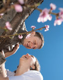 Young man and woman outdoors. Young couple in a blossoming garden Royalty Free Stock Image