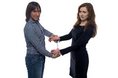 Young man and woman with pair of handcuffs Stock Photos
