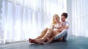 Young man and woman in pajamas sit on floor and pat domestic bunny on her lap. Near big curtained window. happy couple spending leisure time together with their stock video