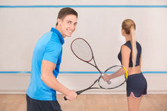 Young man and woman play squash in the gym Royalty Free Stock Photography