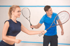 Young man and woman play squash in the gym Stock Image