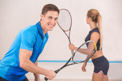 Young man and woman play squash in the gym Royalty Free Stock Images