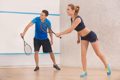 Young man and woman play squash in the gym Stock Photo