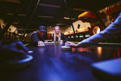 Young man and woman playing air hockey game Stock Image