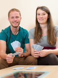Young man and woman playing card game Stock Image