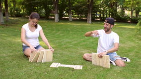 Young man and woman playing giant dominoes in Park stock video footage