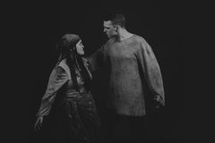 A young man and woman playing the role of the play on a dark background Stock Image