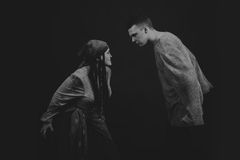 A young man and woman playing the role of the play on a dark background Royalty Free Stock Image