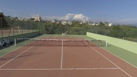 Young man and woman playing tennis in sport resort, panoramic view of court stock video footage