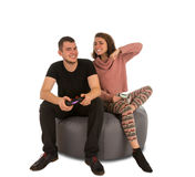Young man and woman playing video games while sitting on round s. Young men and women playing video games while sitting on round shape grey beanbag chair  on Stock Photos