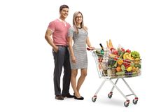 Young man and woman posing with a full shopping cart stock photos