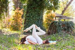Young man and woman practice partner yoga outdoor in wood summer day stock photography
