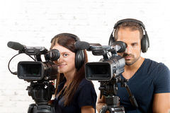 Young man and woman with professional  cameras Stock Photos