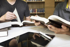 Young man and woman reading book in library Stock Photos