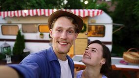 Young man and woman recording video for friends using smartphone or camera. Happy smiling couple in love showing the
