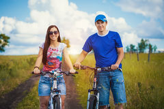 Young man and woman are riding bicycle outside Stock Photo