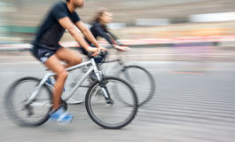 Young man and woman riding bicycles on a city street Stock Photos