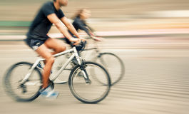 Young man and woman riding bicycles on a city street Stock Photography