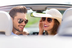 Young man and woman riding in convertible car Stock Images