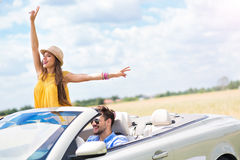 Young man and woman riding in convertible car stock photo