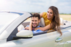 Young man and woman riding in convertible car Royalty Free Stock Photos