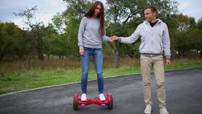 Young man and woman riding on the Hoverboard in the park. content technologies. a new movement. Close Up of Dual Wheel stock video