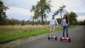 Young man and woman riding on the Hoverboard in the park. content technologies. a new movement. Close Up of Dual Wheel stock video footage