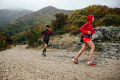 Young man and woman runners athletes run on a mountain trail Stock Photos