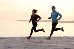 Young man and woman running along the waterfront Stock Photo