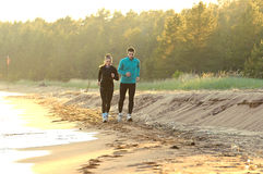 Young man and woman running along the waterfront royalty free stock photo