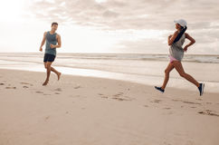 Young man and woman running in morning on beach Stock Photography