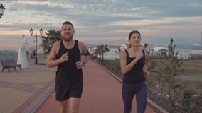 Young man and woman are running in picturesque path in park of city in sunset