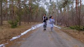 Young man and woman runs together in the winter forest. Young sport people makes morning exercises outdoors. Pretty woman and handsome man wearing sportswear stock video