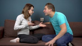 Young man and woman scream at each other. Family quarrels. Couple sitting on the couch against against each other