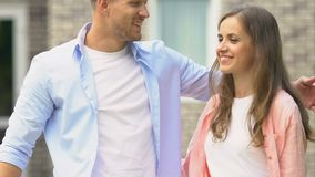 Young man and woman setting for sale sign in house yard, young family relocation. Stock footage stock footage
