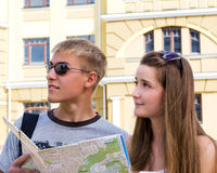 Young man and woman sightseeing. Young men and women sightseeing with a map in front of a hsitorical building facade as they enjoy their summer holiday Royalty Free Stock Photos