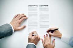 Young man an woman signing a prenuptial agreement. Closeup of a young man an a young woman signing a prenuptial agreement Royalty Free Stock Photo