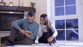 Married couple uses tablet relaxing near fireplace. Young man and woman sits on floor near fireplace in living room and using tablet. Married couple have a good stock video