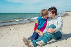 Young man with a woman sitting on the beach and talk Stock Photography