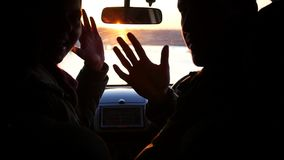 The young man and woman are sitting in the car in the front seat, turning and waving their hands, on a red sunset. Background outside the window stock footage