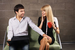 Young man and woman sitting with a laptop Royalty Free Stock Photos